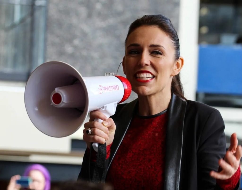 Jacinda Ardern speaking to a crowd using a megaphone scaled